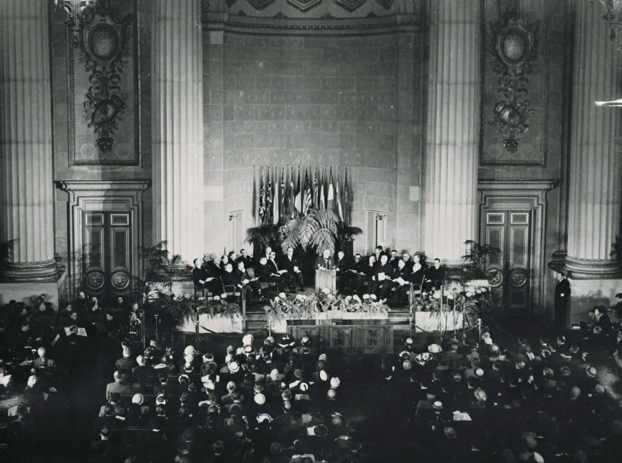 A historic photos shows dozens of delegates assembled in chairs around a podium, with more people seated around a lecturn. Behind there are giant columns.