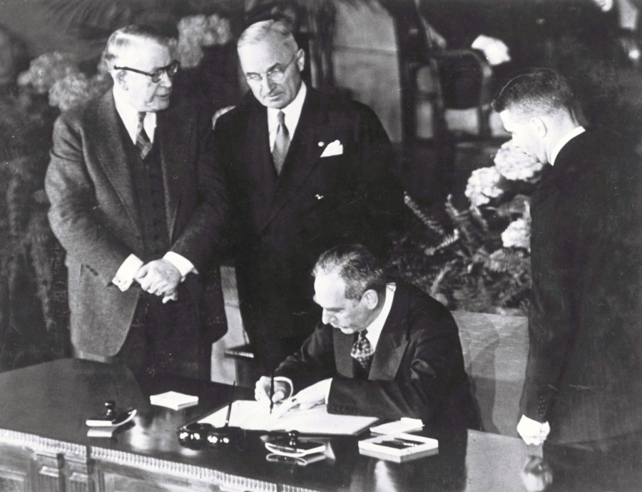 A man signs a piece of paper and two others look on in a historic black and white photo
