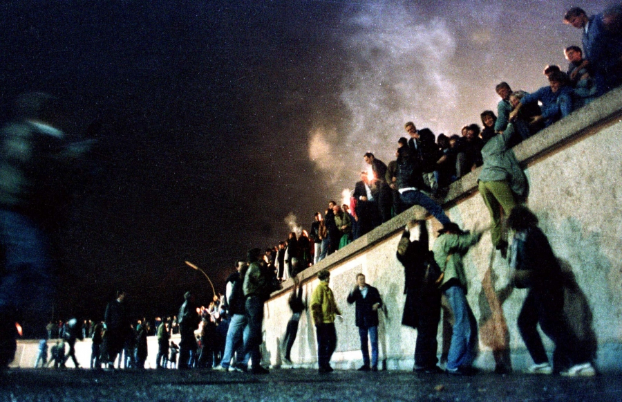 A crowd of people stand atop the Berlin Wall near Brandenburg gate in this 1989 photo. Behind them is smoke from what could be burning fires.