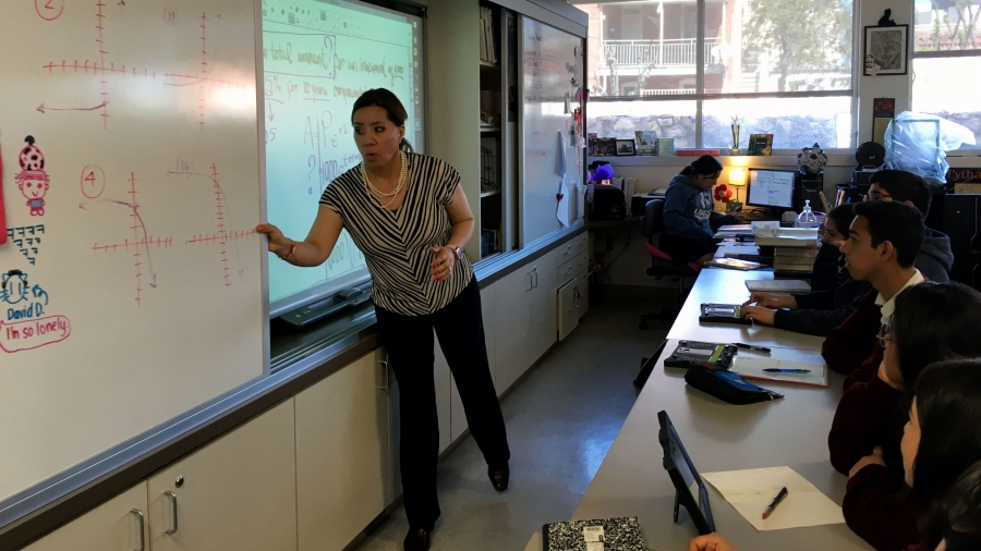 A teacher stands at the front of a classroom