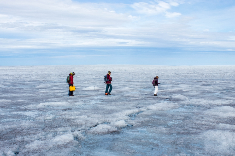 Students Rosie Leone, Aidan Stansberry and Ian MacDowell  are shown bundled in artic-ready clothing and walking across the ice.