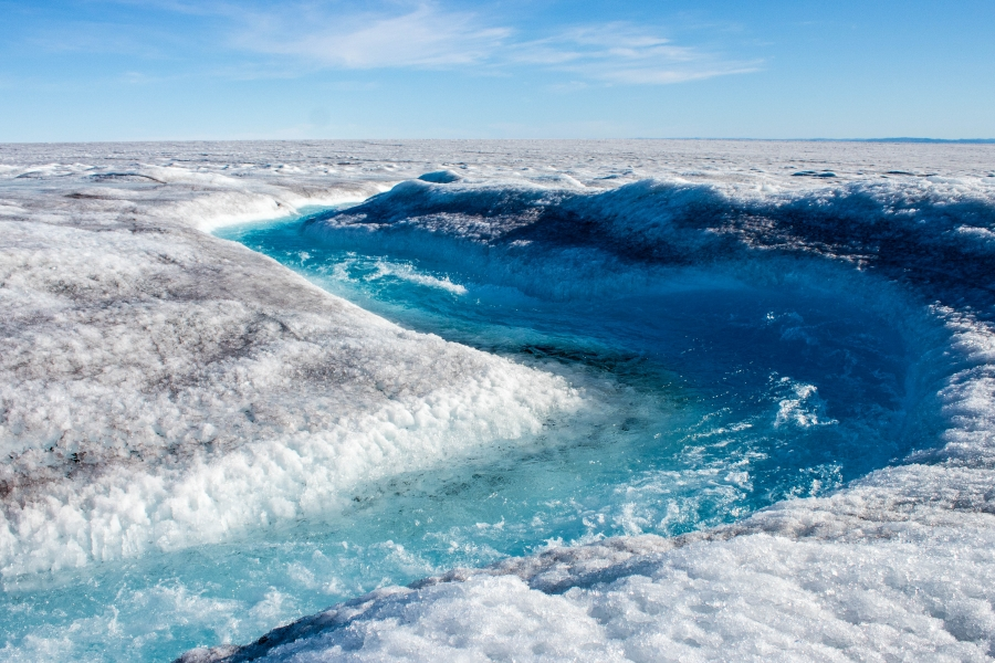 A winding flow of water is shown on the Greenland ice sheet