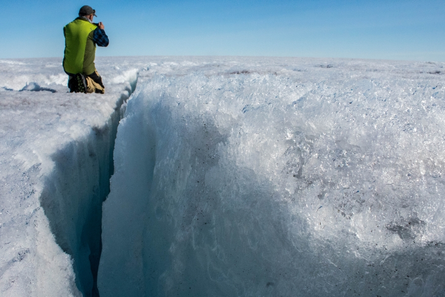 University of Montana glaciologist Joel Harper is shown knealing next to a deep crack in the ice sheet called a crevasse.