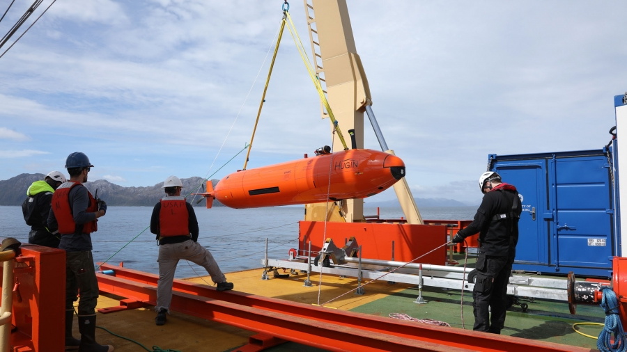 Researchers hoist the orange-colored Hugin autonomous submarine onto the deck of the Nathaniel B. Palmer.