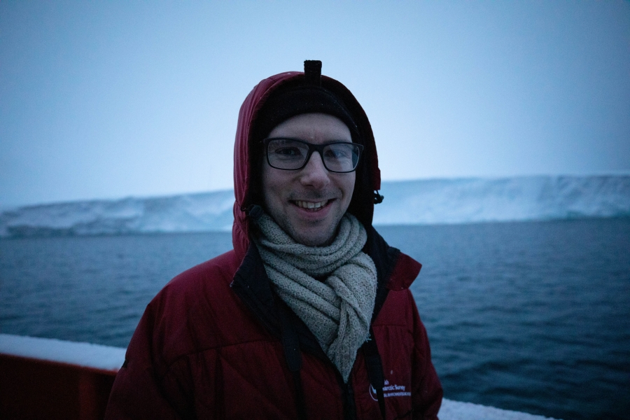 Oceanographer Peter Sheehan is shown with a red jacket and white scarf with Thwaites glacier in the background.