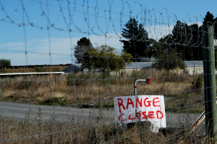 "A sign is seen through a chain link fence with a wooden sign reading, ""range closed."""