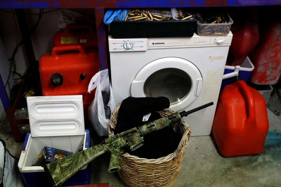 An AR-15 semi-automatic rifle is seen painted in camoflage and sitting on a laundry basket.