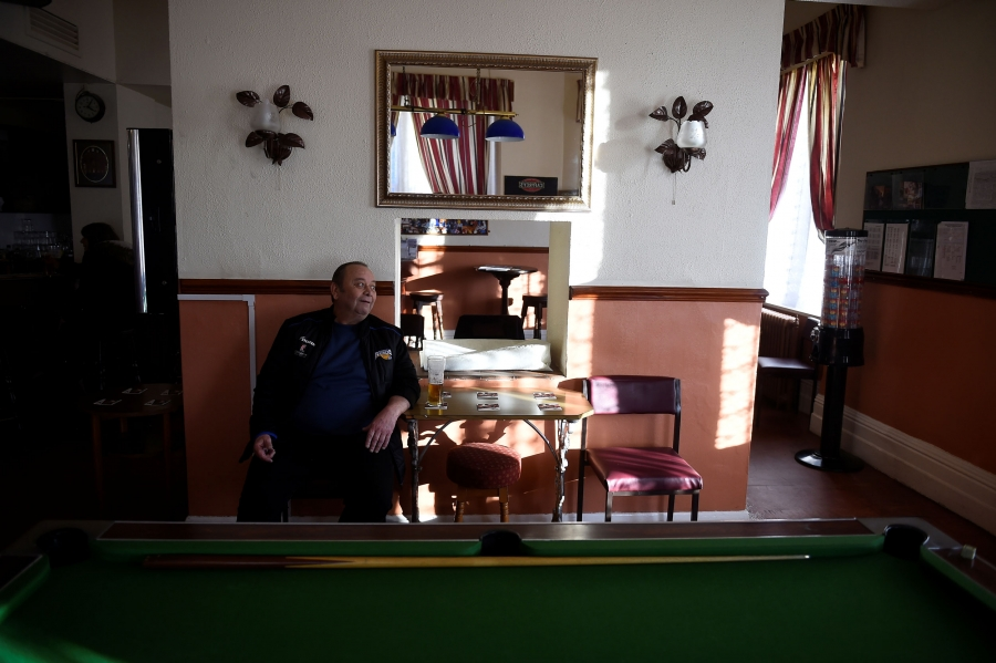 A man is shown sitting down with a pint of beer behind a billiards table.