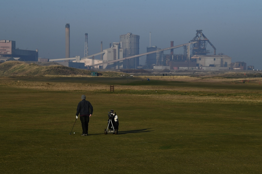 A man is show walking with a golf bag with an industrial steelworks plant in the background.