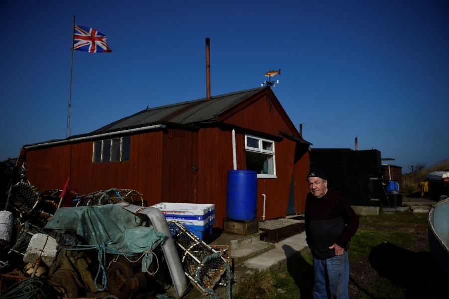 Mohan walks by a red, wooden fishing hut that has a British flag flying behind it.
