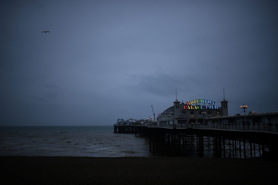 A large building is shown at the end of a pier with a sign illuminated with rainbow colors.