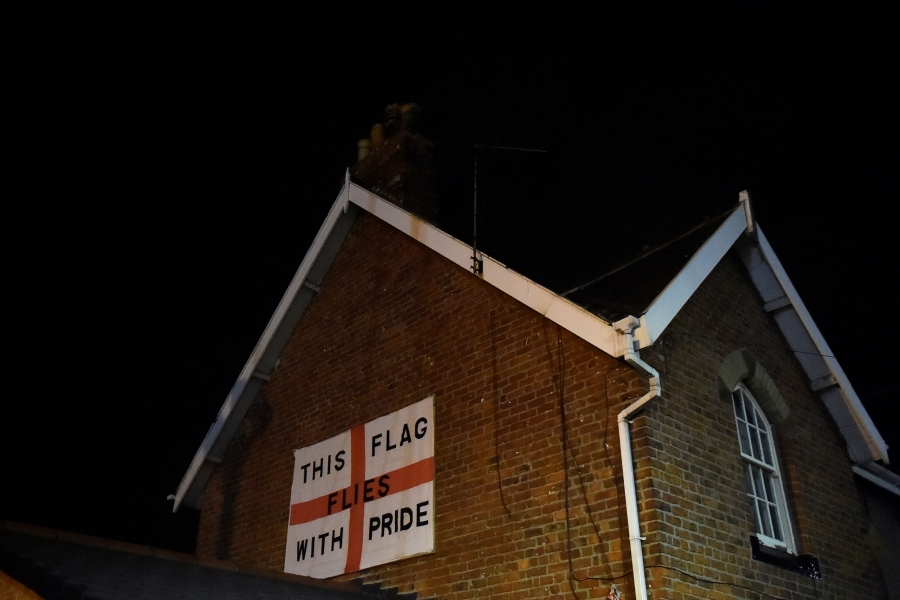 An England flag bearing the words: 'This flag flies with pride' is affixed to the side of a red brick house with white trim.