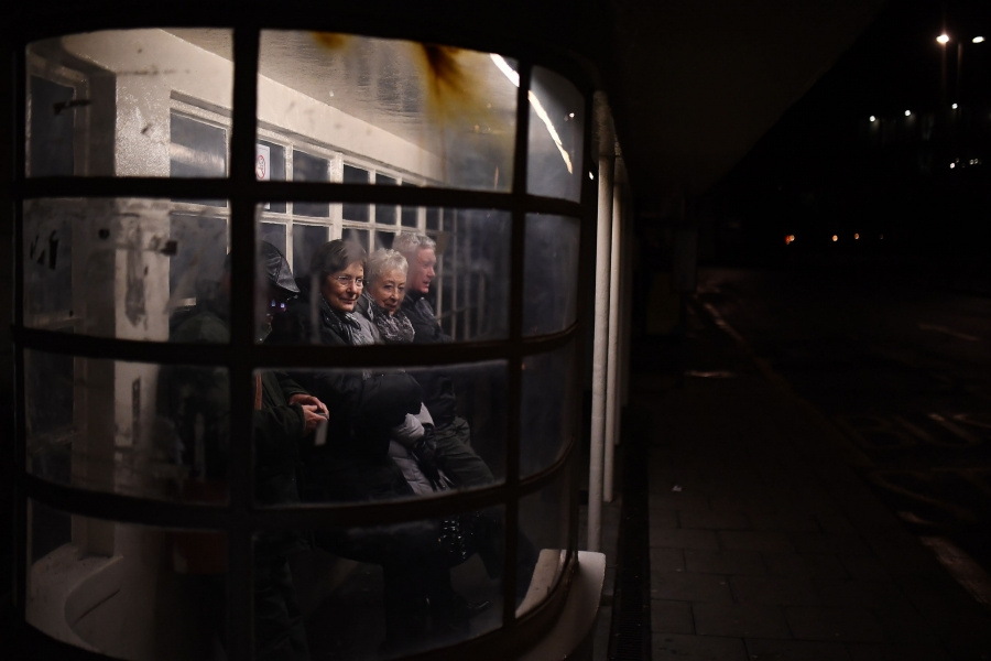 Several older people are shown leaning against the wall of a glass bus stop.