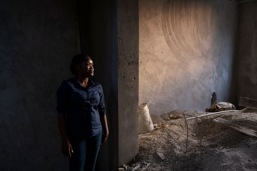 A woman is shown standing among the construction materials of her home with cement walls.