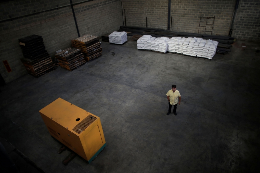 In a photograph taken from above, a man in a yellow shirt is shown standing in a nearly empty warehouse.