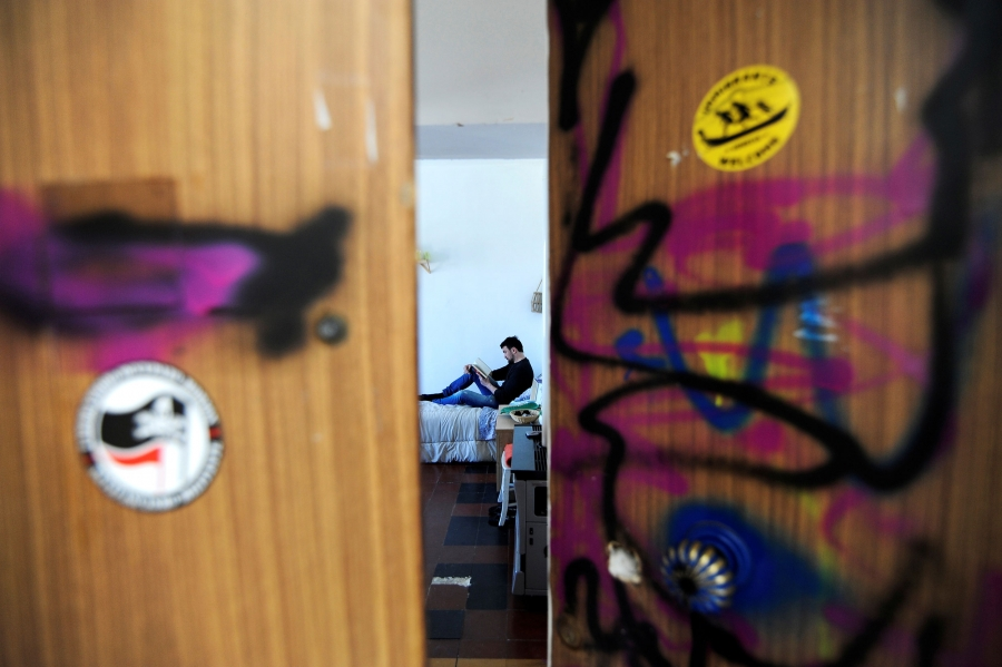 Alessandro Dus is shown through graffiti-painted doors, sitting on a bed reading a book.
