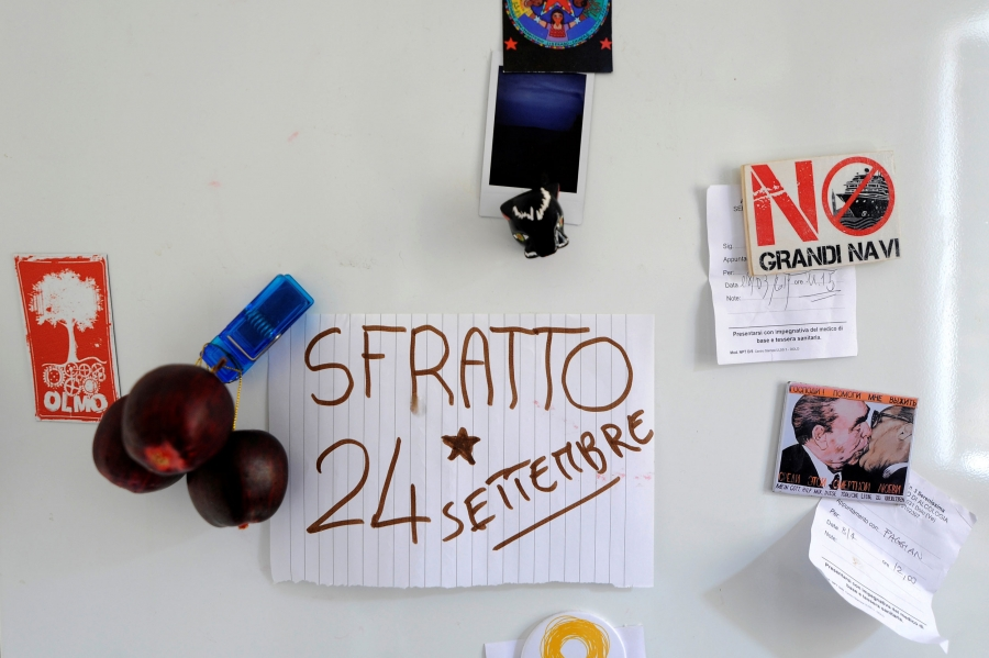 "A note on line paper is seen on a white refrigerator with ""Sfratto 24 Settembre"" written on it."
