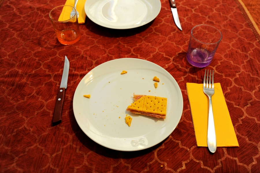A cracker and peanut butter snack snack is seen on the table with a red table cloth.