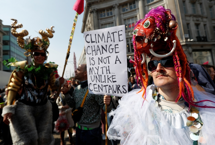 A man with a mask in a crowd of protesters. Someone holds a sign reading: Climate change is not a myth unlike centaurs.