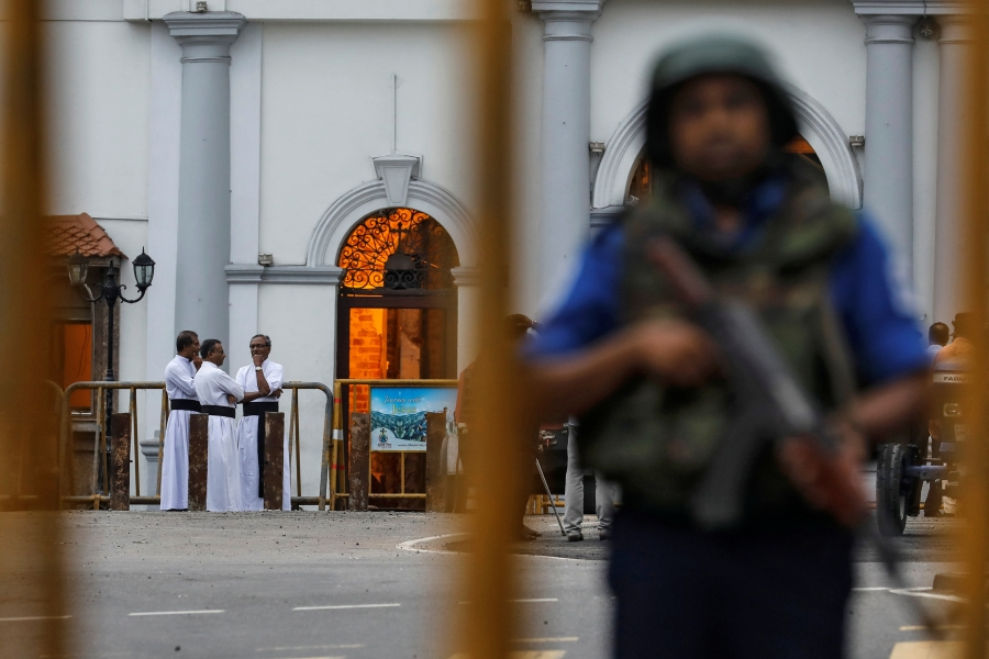An armed man stands guard with priests in the background