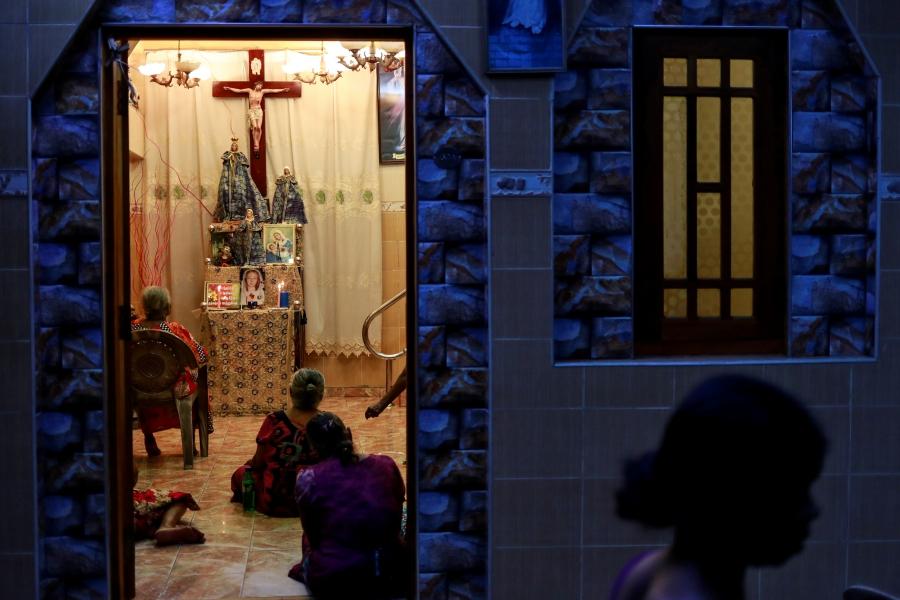 Women kneel before a cross, seen through a doorway