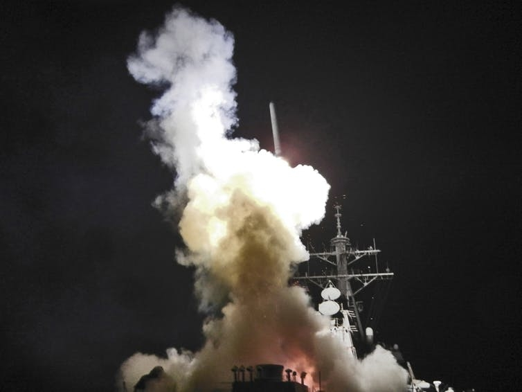 Smoke fills the air as a missile is launched from a military boat at night.