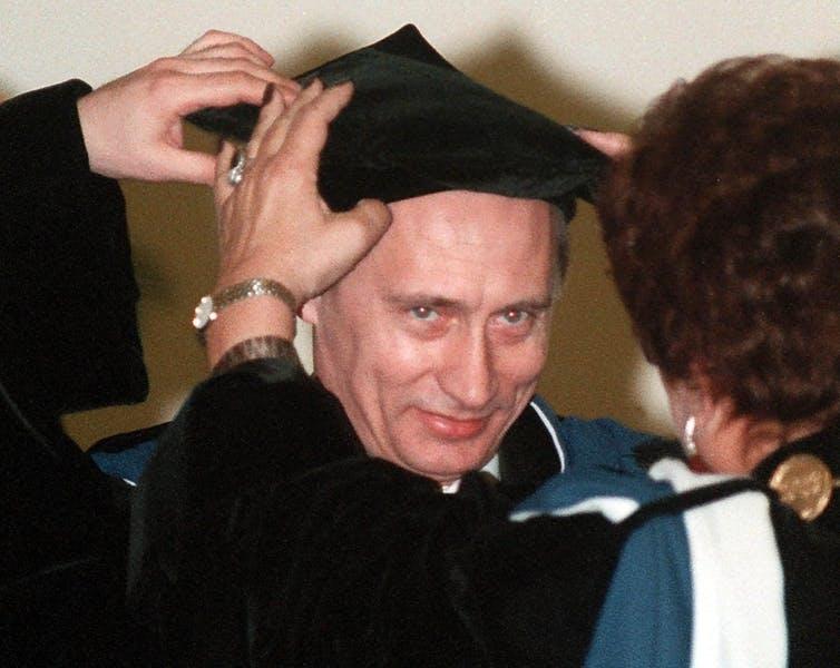 Vladmir Putin is pictured wearing a graduation cap.
