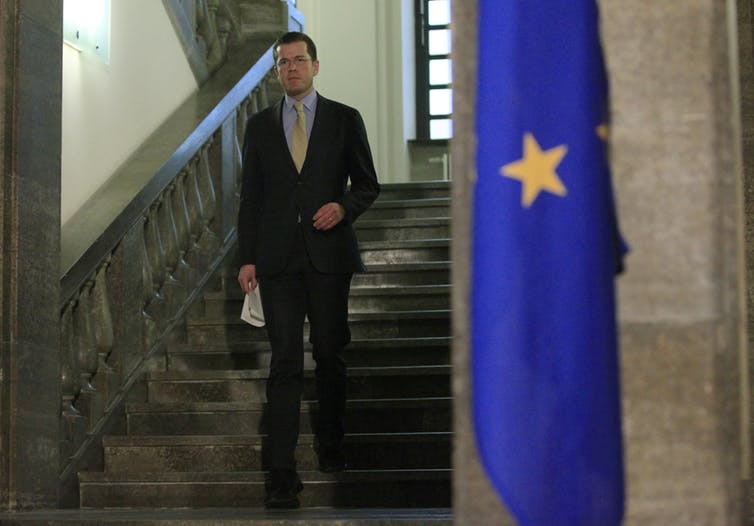 A man stands on a staircase next to a European Union flag.