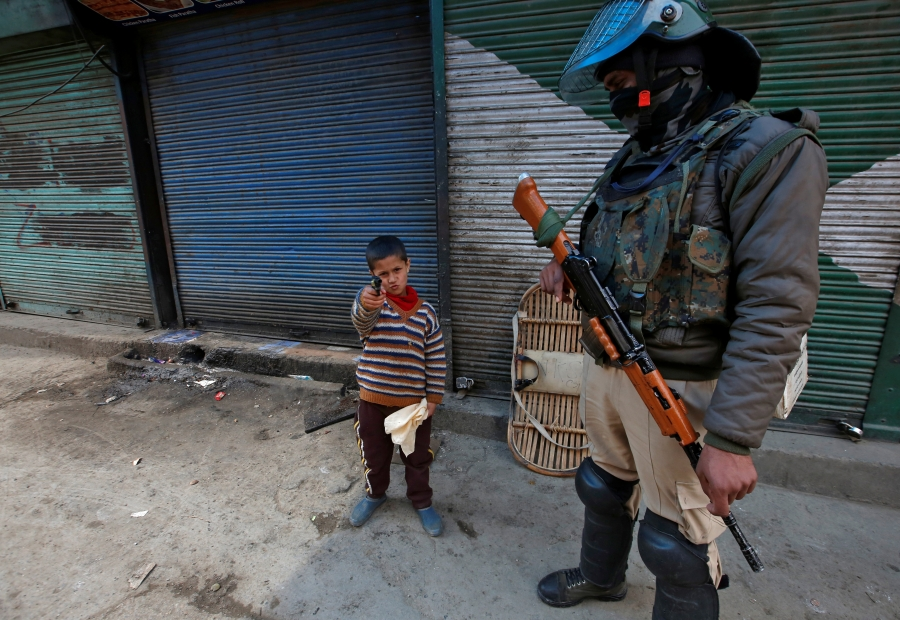 boy stands with pistol next to Indian soldier