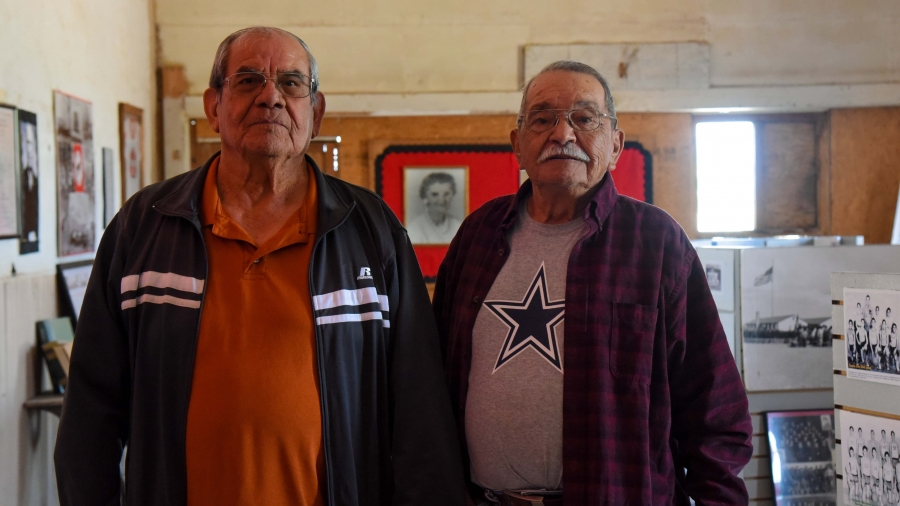 Two older Mexican American men pose for a photo.