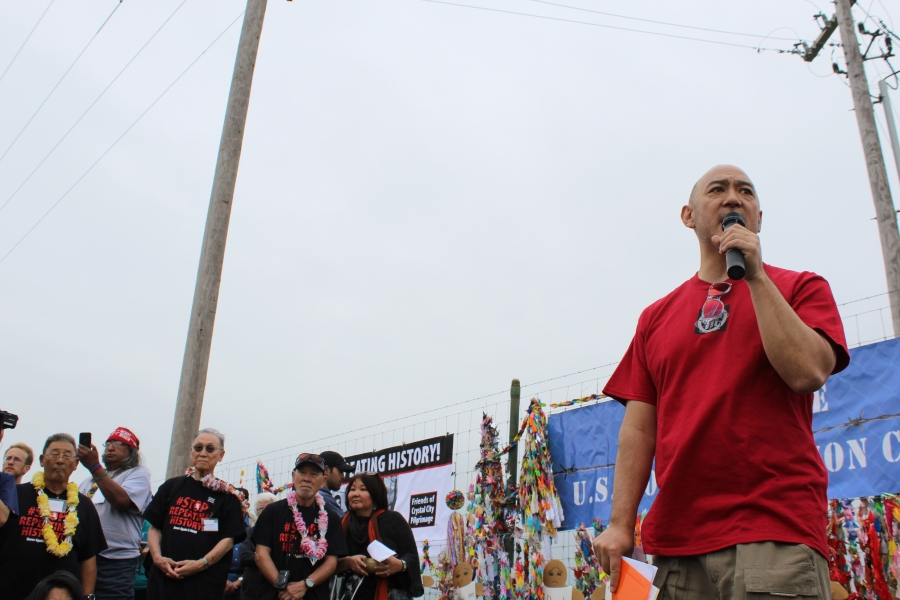 A man stands with a microphone addressing a crowd, with a fence in the background.