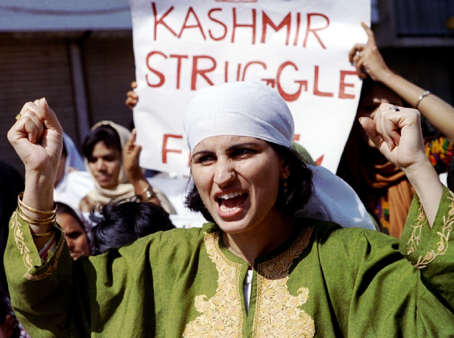 Woman in green shouts in front of Kashmir struggle sign.