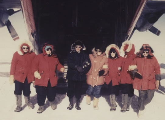 Six women wearing red parkas and a man in black pose for a photo.