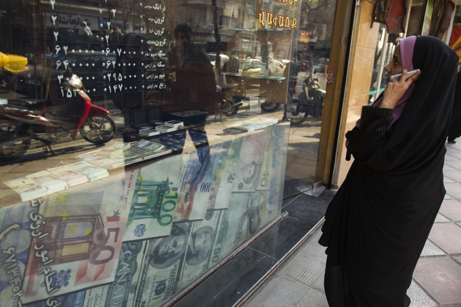 A woman looks through a window decorated with large currency notes