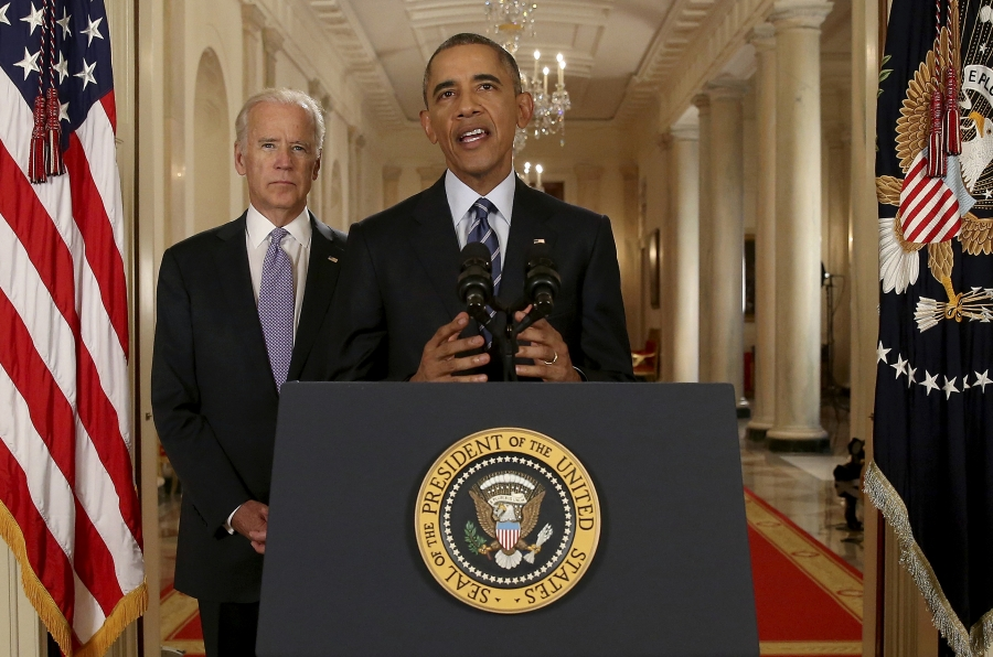 A black man stands behind a podium with the presidential seal. A white man stands behind him. There is an American flag in the corner.