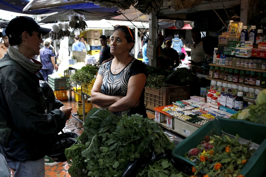 A vendor talks with a customer in her fruit and vegetables stall selling medicines at a market in Rubio, Venezuela.