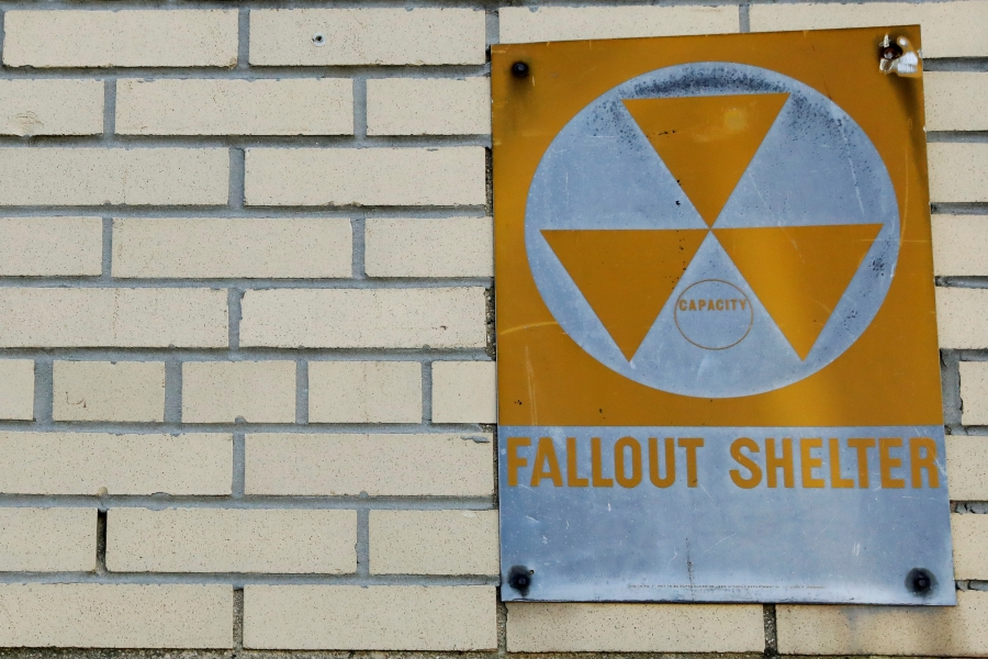 A yellow nuclearfalloutsheltersign is seen hung on a brick building