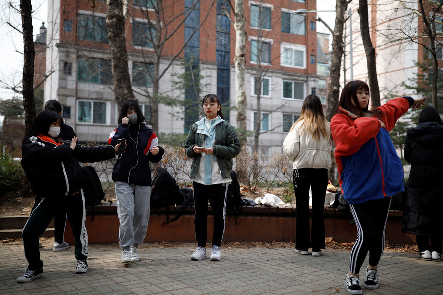Young women are shown doing dance moves in an outdoor park.