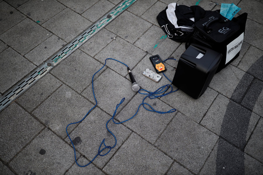 A microphone is shown laying on the ground connected to a small amplifier.