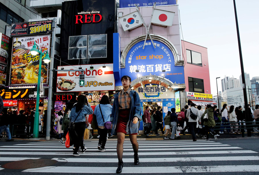 A woman is shown walking across a large street with billboard-clad buildings in the background.