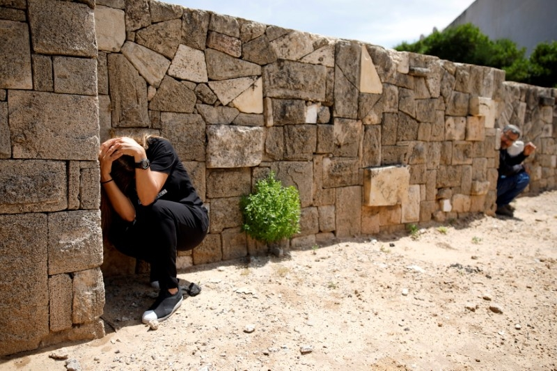 Two people cover their heads next to a wall.