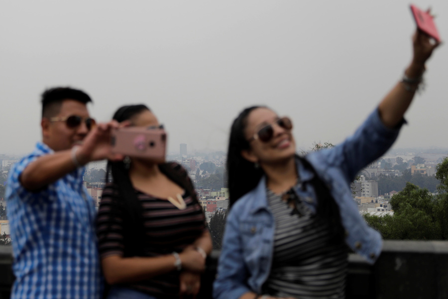 Blurry people in the foreground take a selfie with smog-covered city in the background.
