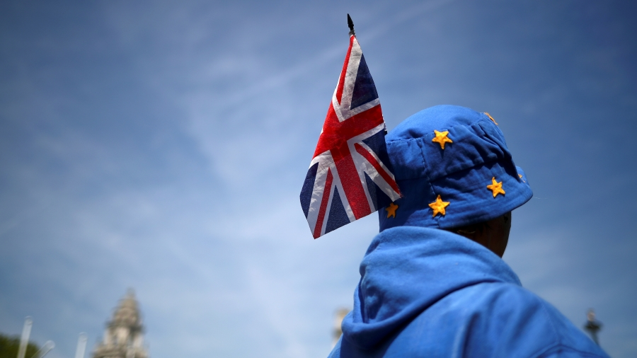 A man in blue with stars on a cap and a UK flag in his had stands with his back facing the camera.