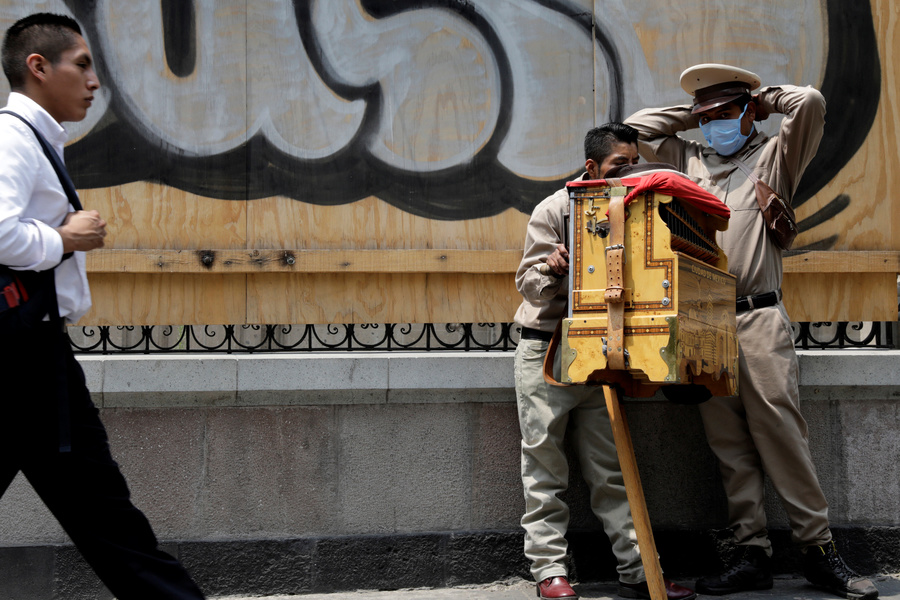 An organ grinder wears a surgical mask on a sidewalk as a man walks past.
