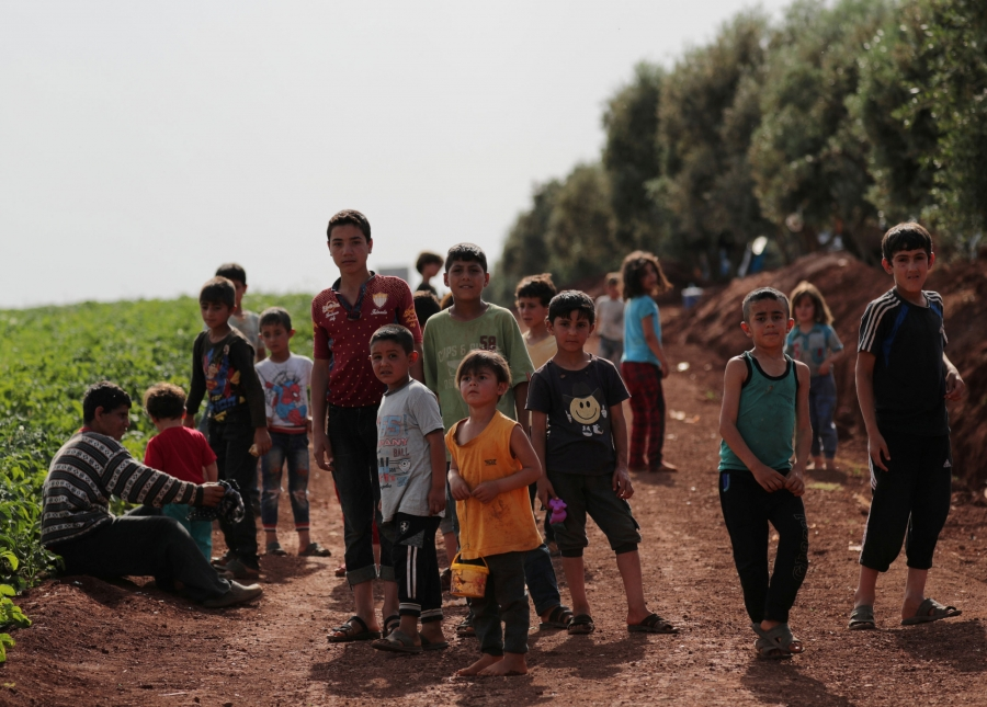 A group of more than a dozen children of varying age are shown standing in a dirt road next to a field.