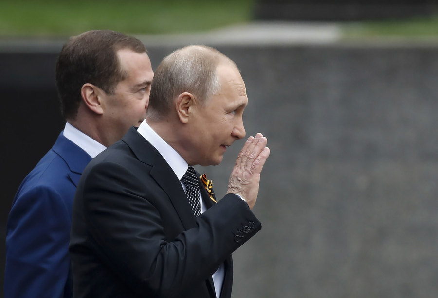 Russian President Vladimir Putin is shown waving with Prime Minister Dmitry Medvedev slightly behind him.