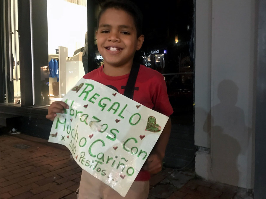 A young boy holds a sign selling hugs for 100 pesos