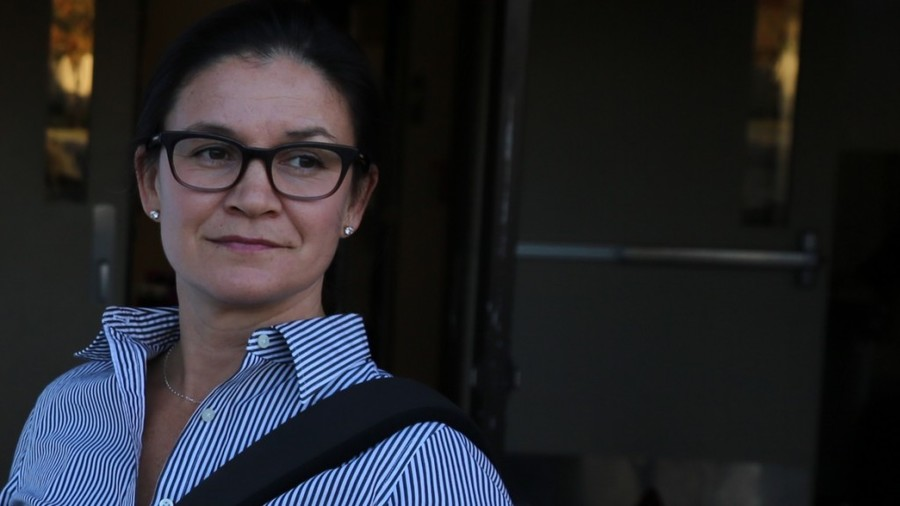 A woman wearing glasses is looking off-camera.
