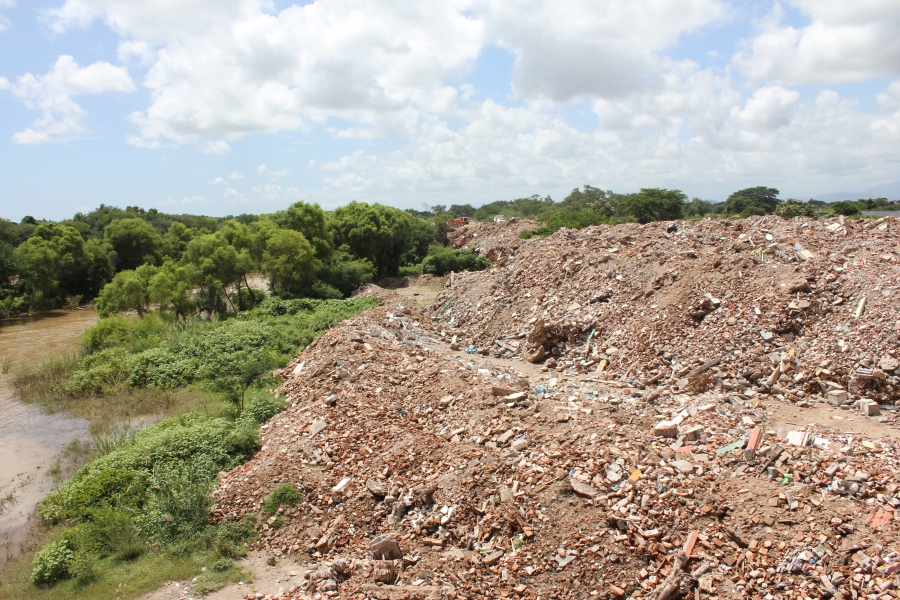 dumping thousands of tons of unsorted rubble along the banks of the Los Perros River in Ixtaltepec