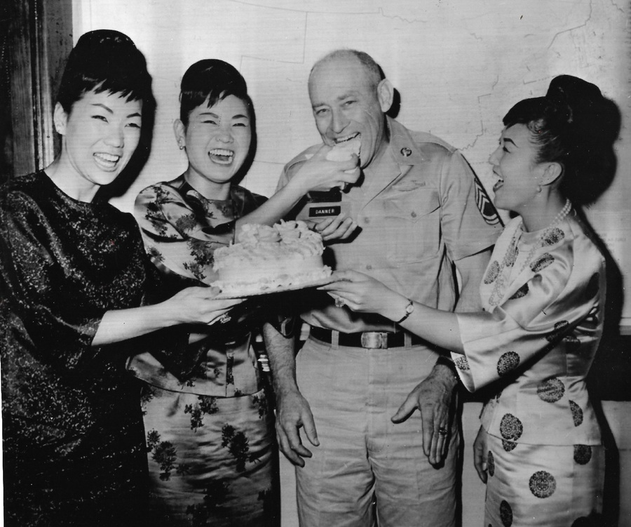 Three Korean women and one man in a military uniform laugh over cake